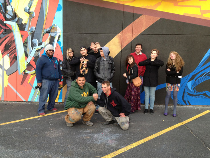 A group of ten young artists posing in front of the mural they have just finished. Two of them are kneeling and shaking hands.