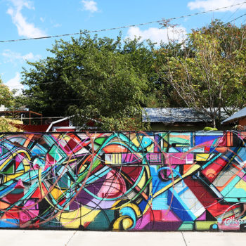 Crazy and colorful photo of a mural that has been spraypainted on a freestanding wall.