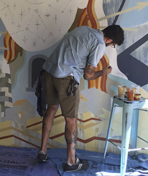 A photo of the young tattooed artist in shorts with his back turned painting the mural in progress.