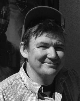 Headshot of the artist Larry Bob wearing a hat and smiling at the camera.