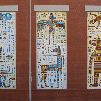 A photo of a three murals side by side on a builinding of abstracted people and animals made up of tiny boxes and stuff.