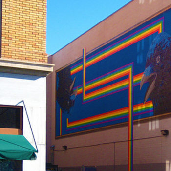 Photo in a small alley of a large mural with a stylized rainbow and two crow heads. One is upside-down.