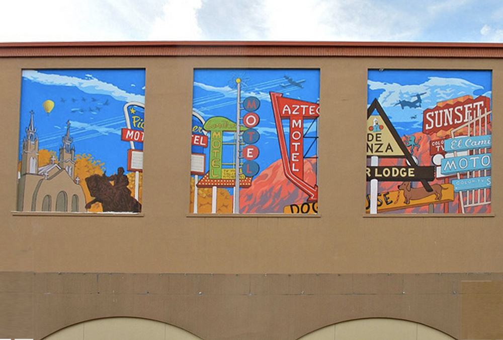Photo of three murals side-by-side on a building wall of historical signs along Rt66 in Albuquerque.
