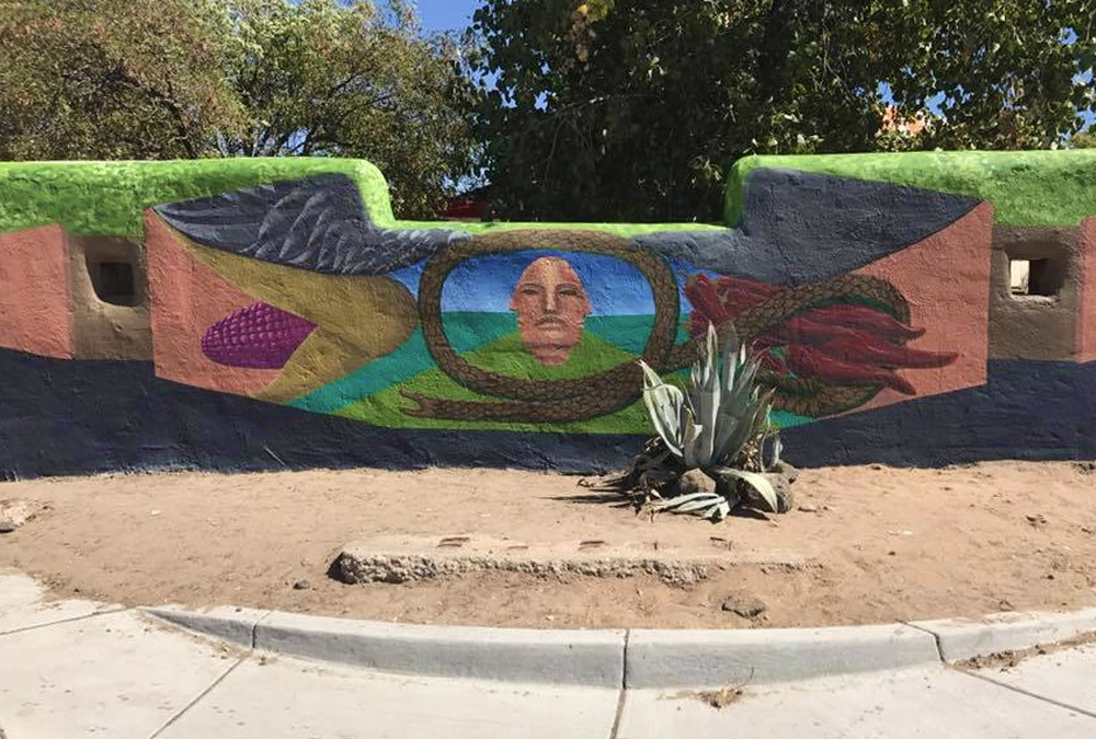 Mural on freestanding wall of a face and birdsongs coming from the frame.