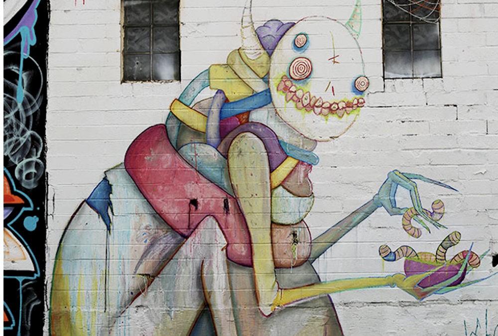 Creepy but cute creature painted on the side of a wall as a mural. Looks like it lives in a fabric store.