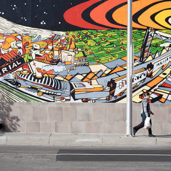 Photo of person walking infront of a colorful and fun mural of downtown Albuquerque.
