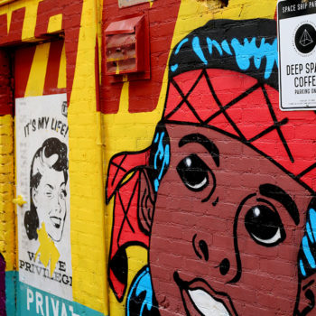 Close up photo of a colorful comic inspired mural that has a young indian boy painted on it in the style of superman.