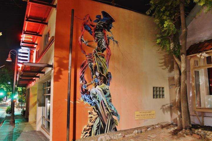 Tall mural of a futurist totom-pole of high-tech superhero capes