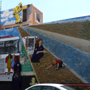 Funny 3D mural of firemen and firetrucks. Sticks out of wall maybe 10 inches in parts.