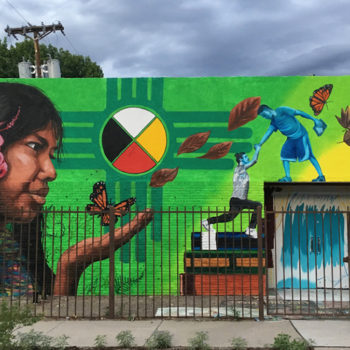 girl discovers butterfly against New Mexico symbol mural