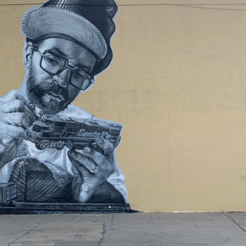 black and white mural of man painting model train