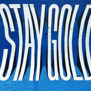 mural of fish-eyed letters reading stay gold