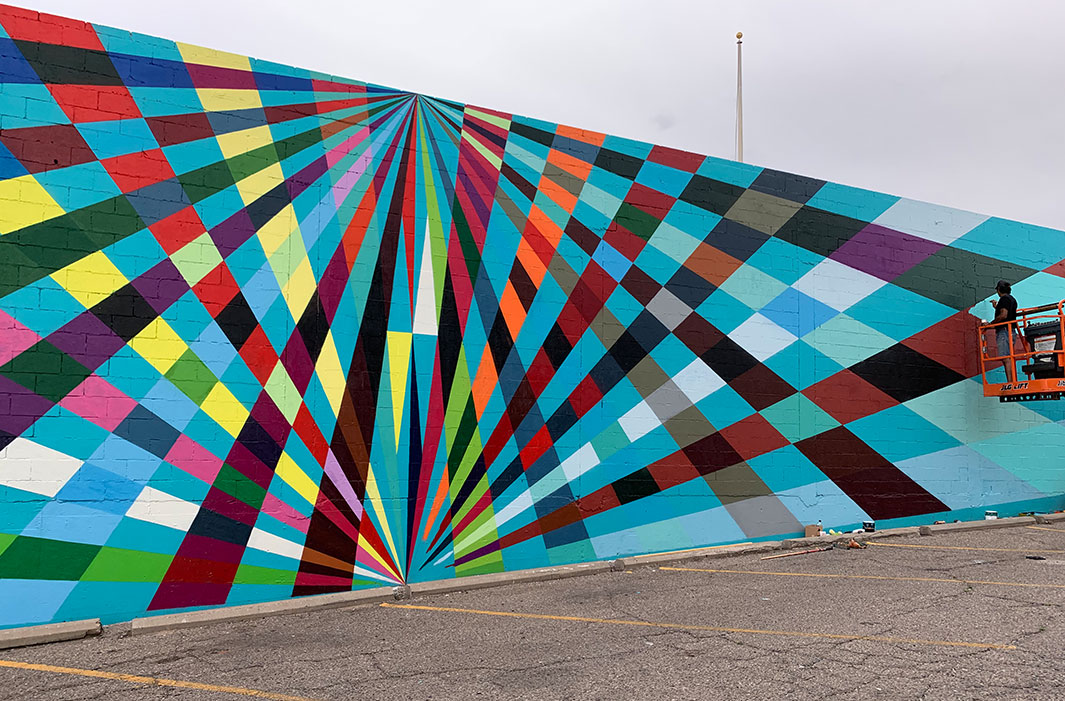 man painting mural of overlapping rays