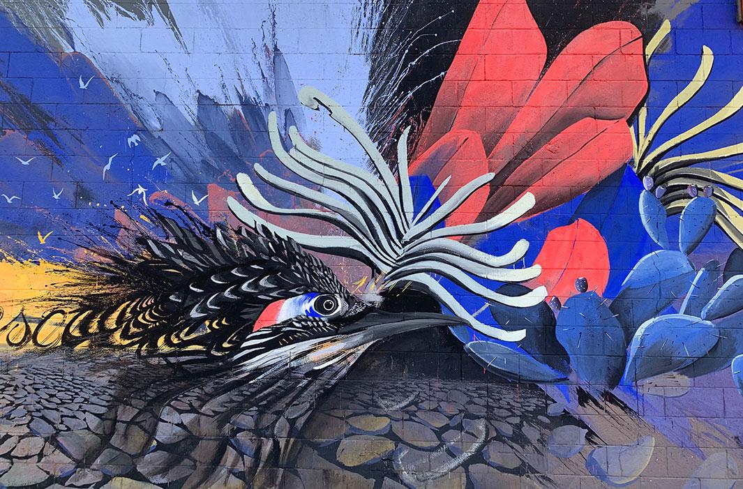 mural of woodpecker merging with cactus flowers