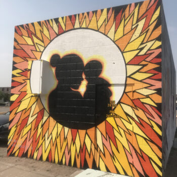 Silhouette of mother and child inside a sunburst