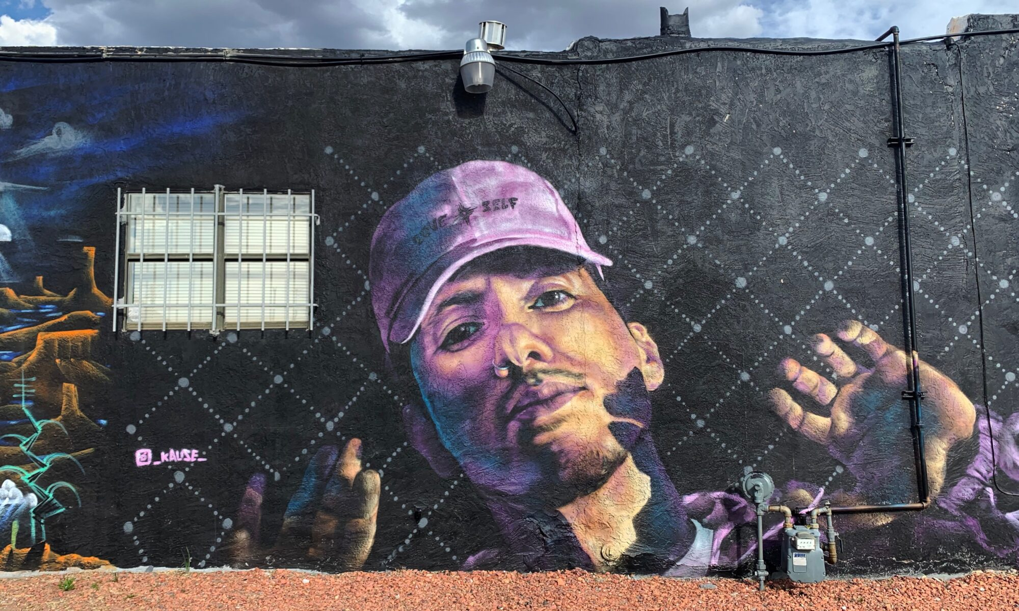 man wearing cap with mural title on it