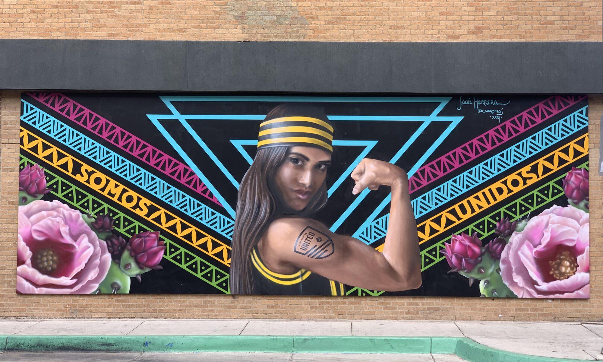 Woman Wearing NM United Attire Flexing Arm